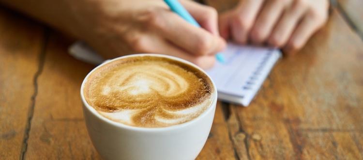 Egy jegyzetelő kéz reggeli kávéval